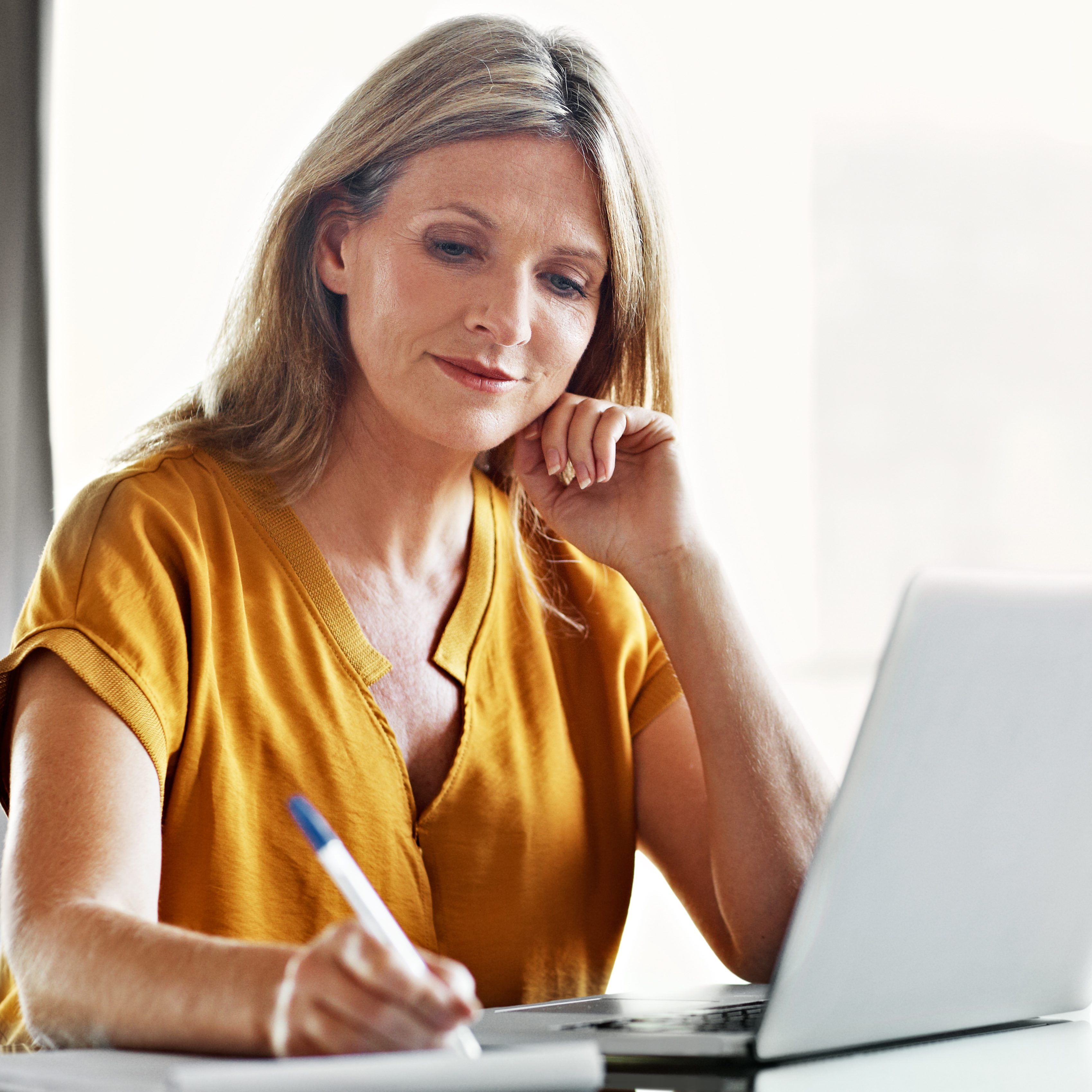 Shot of a mature woman using a laptop at home to research blepharoplasty.