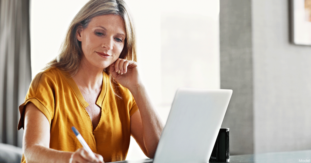 Woman on laptop jotting down notes