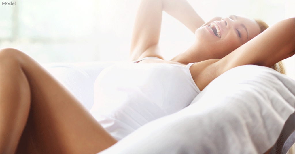 Woman lying in bed happy about her breast surgery results from a Toronto plastic surgeon