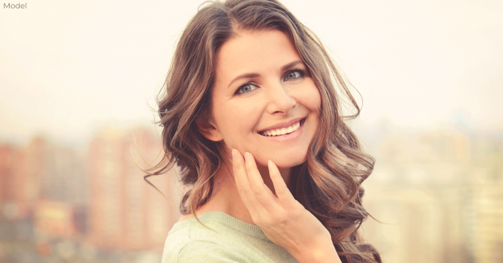 Woman with hand to her cheek and smiling